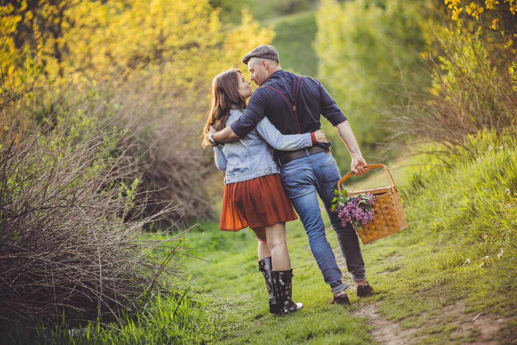 Man and woman walking in the woods on a picnic in a happy mood