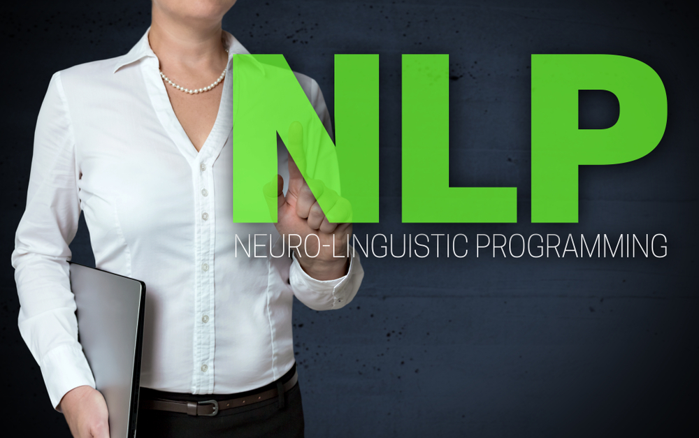 Woman pointing to words that say NLP Neuro-Linguistic Programming