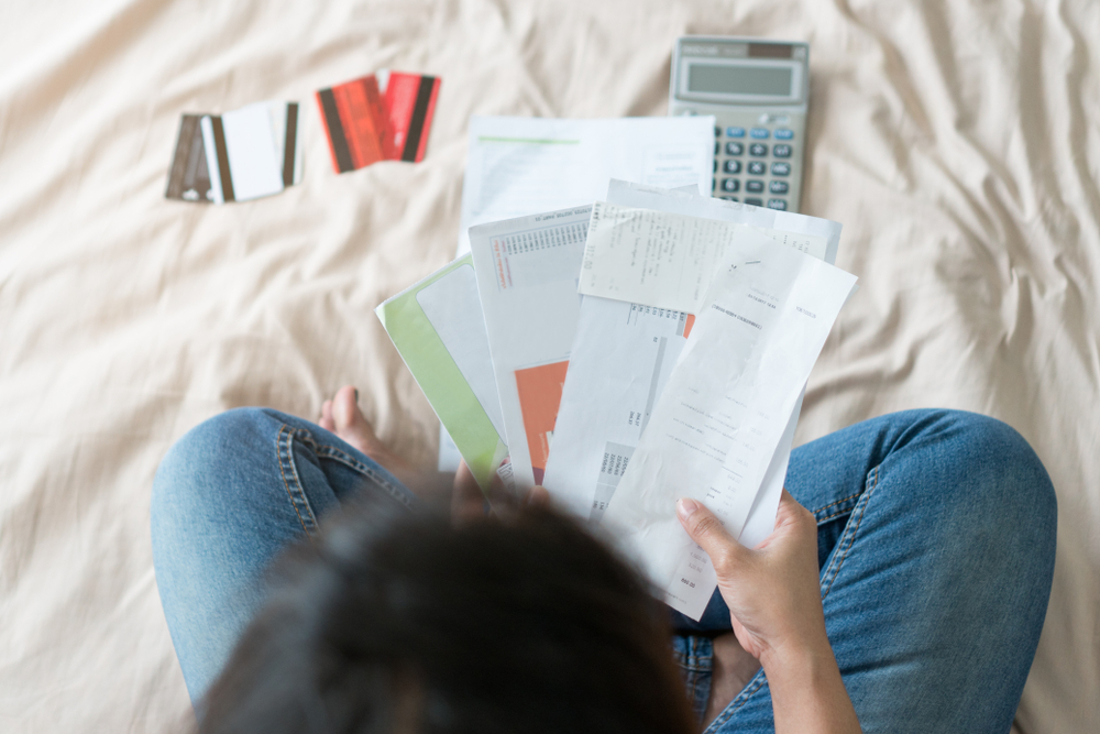 woman reviewing bills with a calculator
