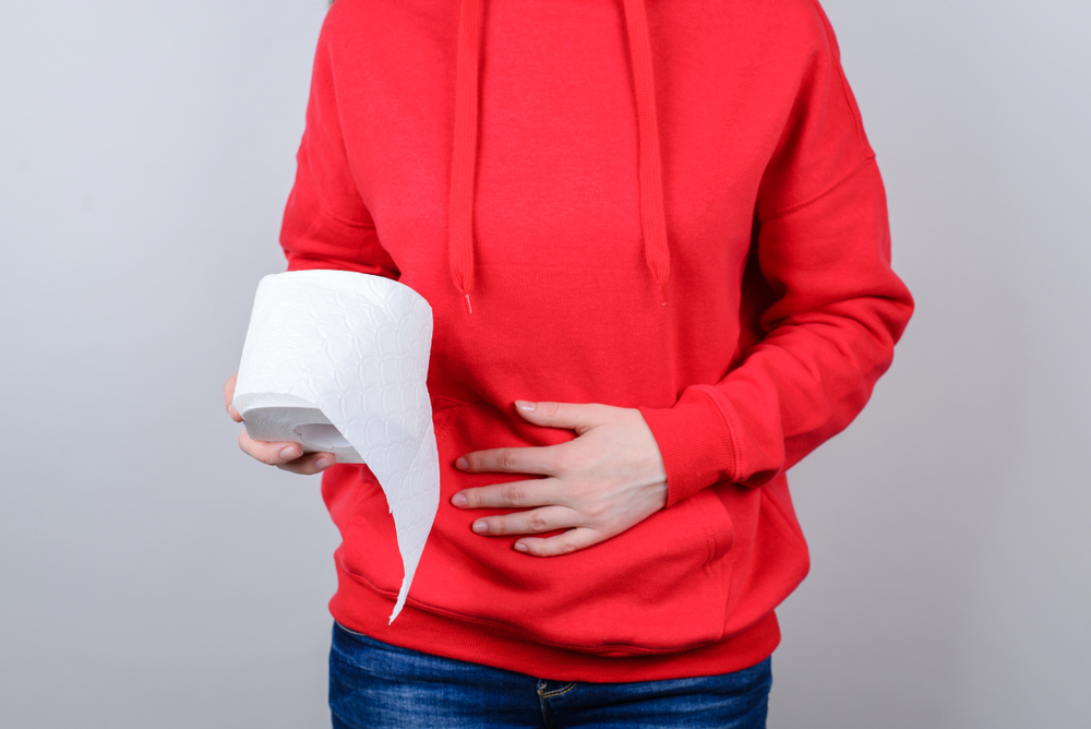 Unhappy woman holding her gut with one hand and a roll of toilet paper in another