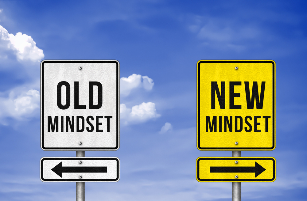 two signs pointing in opposite directions saying Old Mindset and New Mindset